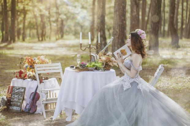 девеста сидит на стуле на природе рядом с накрытым белой скатертью столом