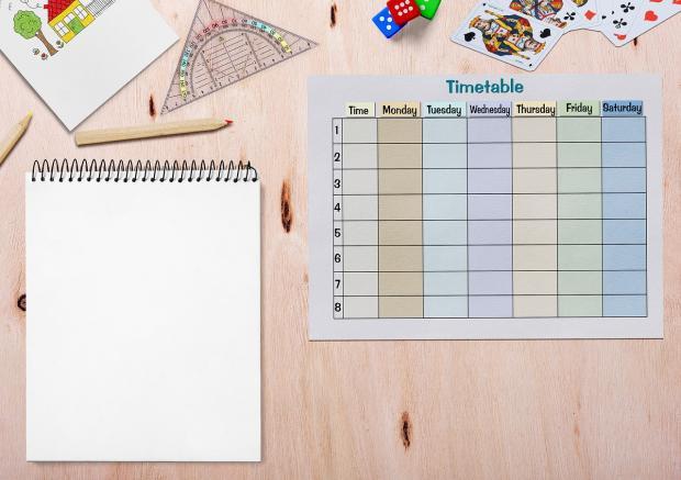на деревянном столе лежат блокнот с графиком на дни недели и канцелярскими принадлежностями