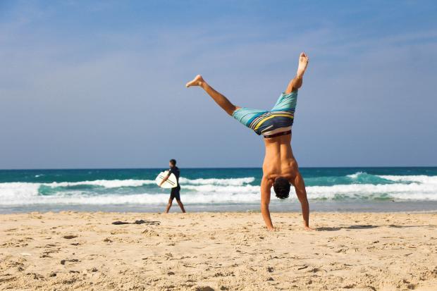 парень стоит на руках на пляже