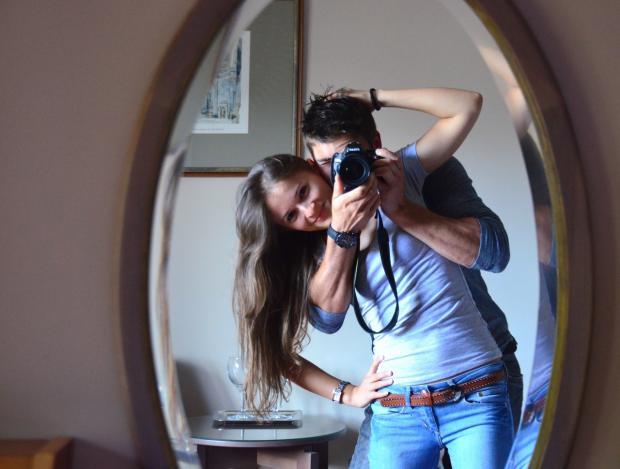 мужчина и девушка фотографируются у зеркала