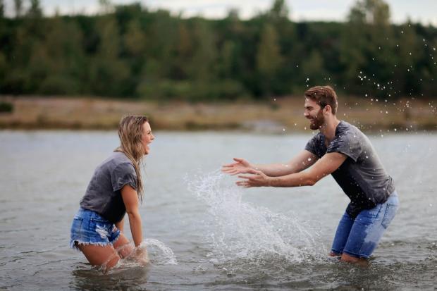 девушка и мужчина в джинсовых шортах и серых футболках брызгают друг на друга водой в реке
