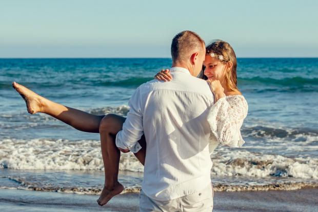 мужчина несет на руках девушку по берегу моря
