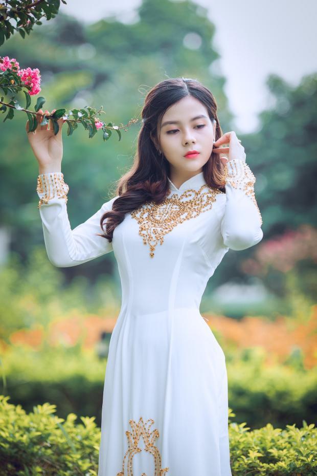 в саду стоит девушка в красивом белом платье с орнаментом