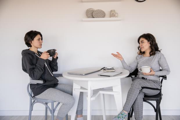 две девушки разговаривают, сидя за столиком