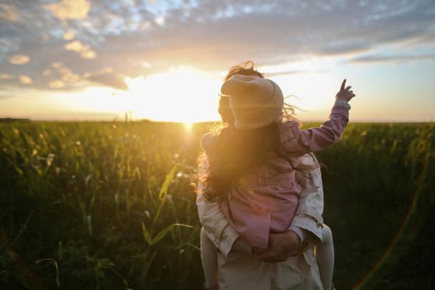 женщина с ребенком на руках на фоне заката