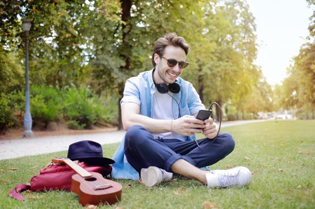 молодой мужчина сидит на земле в парке