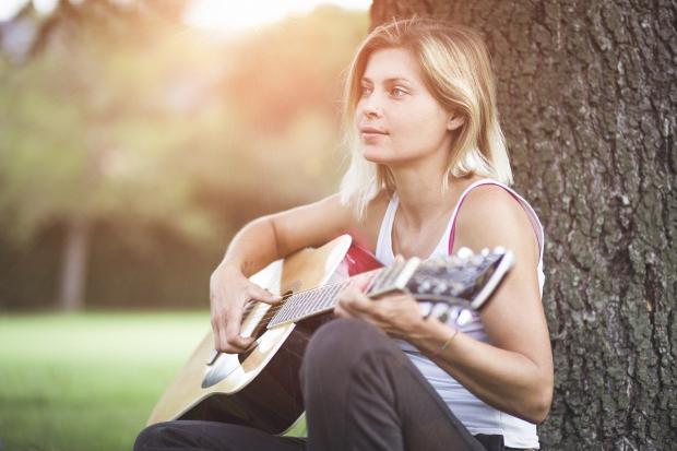 девушка сидит у дерева и играет на гитаре