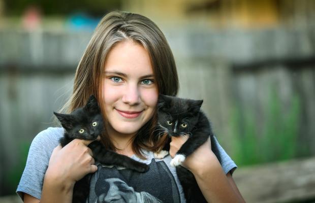 молодая девушка держит в руках двух черных котят