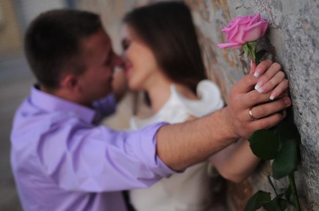на свидании девушка с розой в руках и мужчина с обручальным кольцом