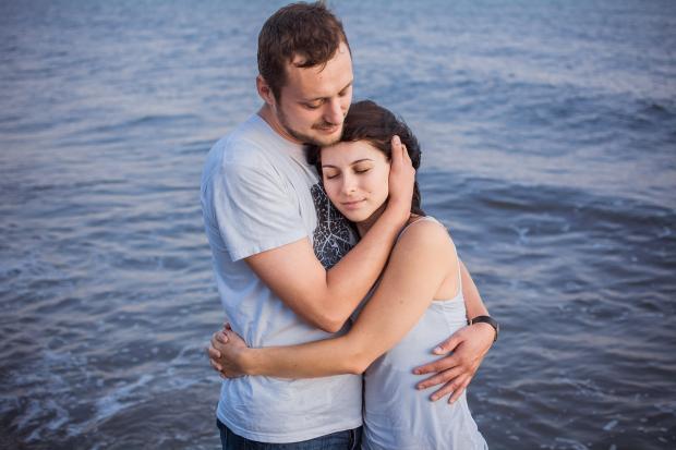 мужчина и девушка обнимаются на берегу синего моря