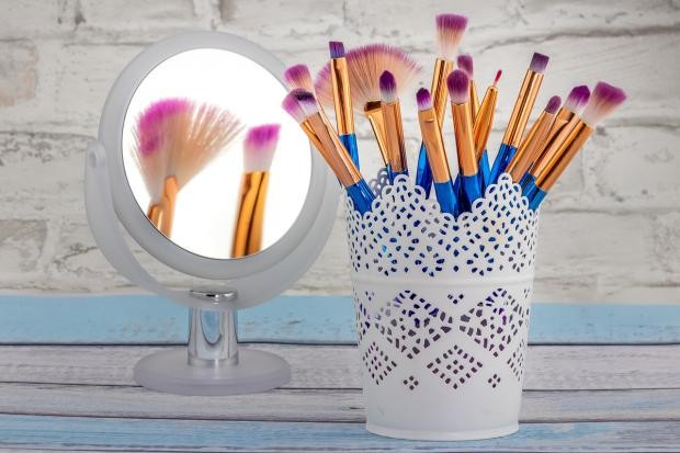 в белом декоративном стакане стоят кисти для нанесения макияжа