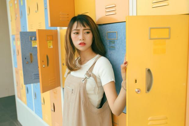 невысокая девушка в белой футболке и сарафане стоит на фоне ярких шкафчиков