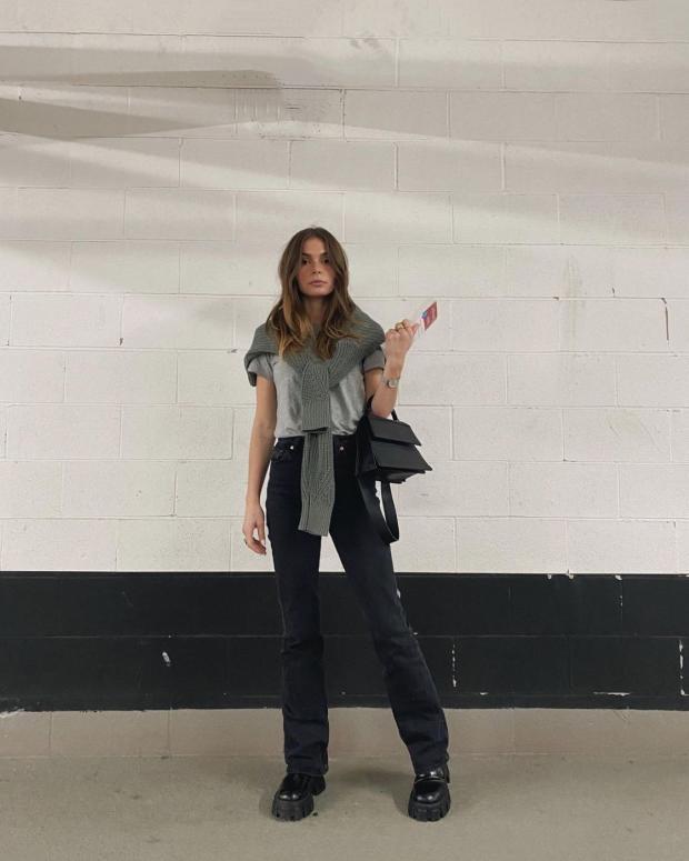 стоит девушка в модных джинсах