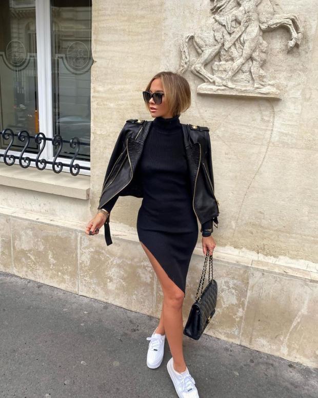 идет девушка в черном обтягивающем платье с разрезом на боку