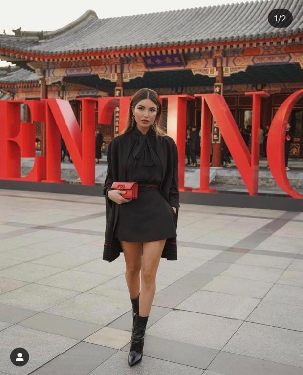 девушка держит в руках маленькую красную сумочку