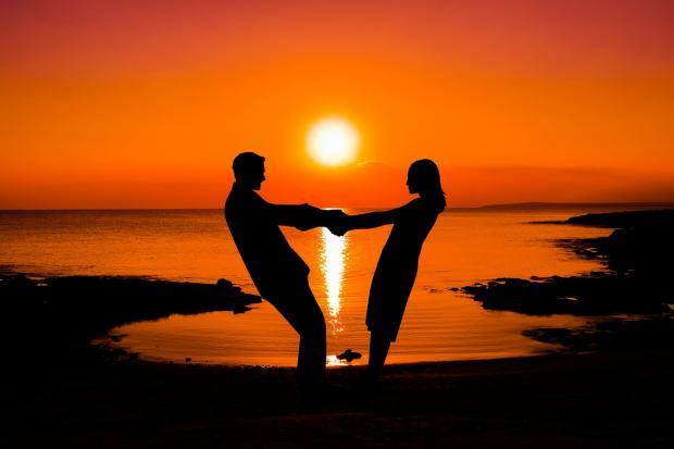 два силуэта на фона заката над морем