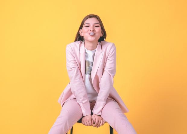 девушка в розовом костюме на фоне яркой желтой стены