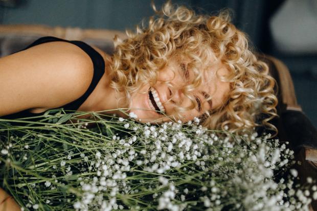 кудрявая девушка с букетом белых цветов