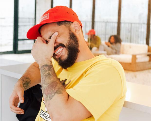 смеющийся молодой мужчина в желтой футболке и красной кепке