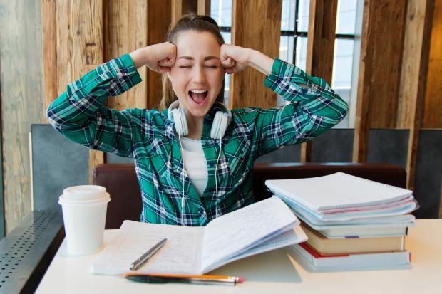 девушка сидит перед учебниками, руки у головы