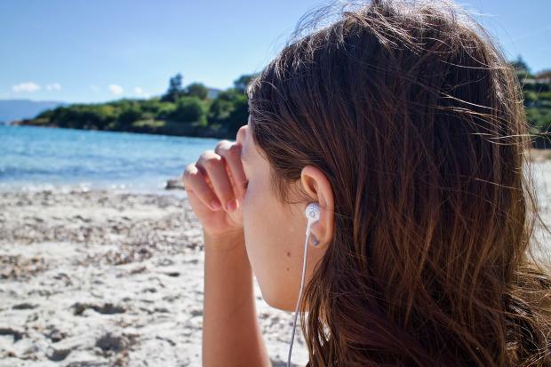 девушка в наушниках сидит на берегу и смотрит на море
