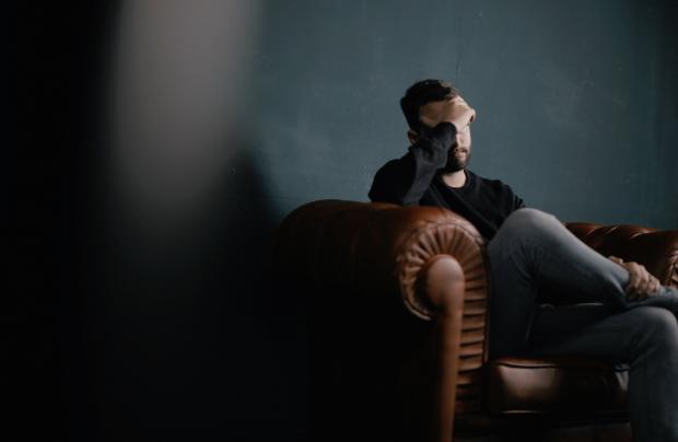 мужчина сидит на кресле и держится за голову