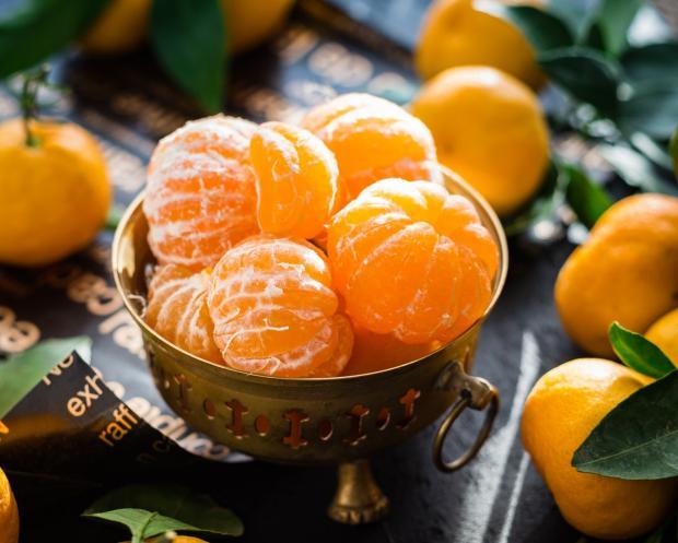 в металлической вазе лежат очищенные апельсины
