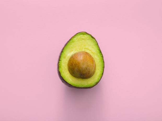 на розовом фоне лежит половинка авокадо с косточкой