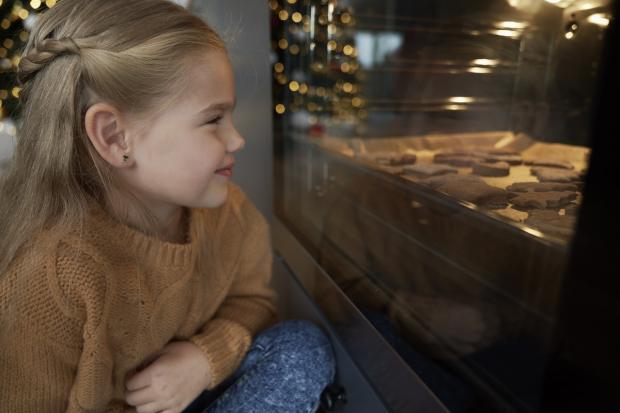девочка смотрит через стекло духовки на печенье