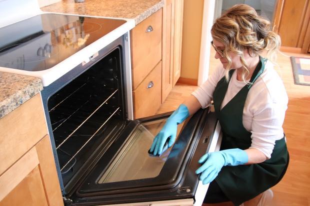 женщина моет дверцу духовки