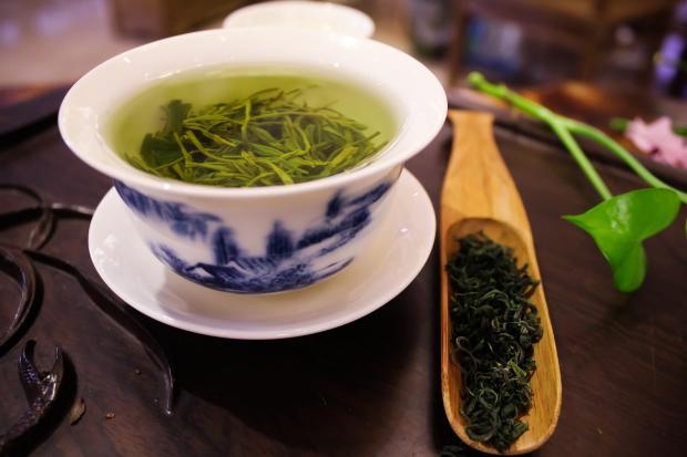 зеленый чай в чашке, чайные листья в деревянной ложке