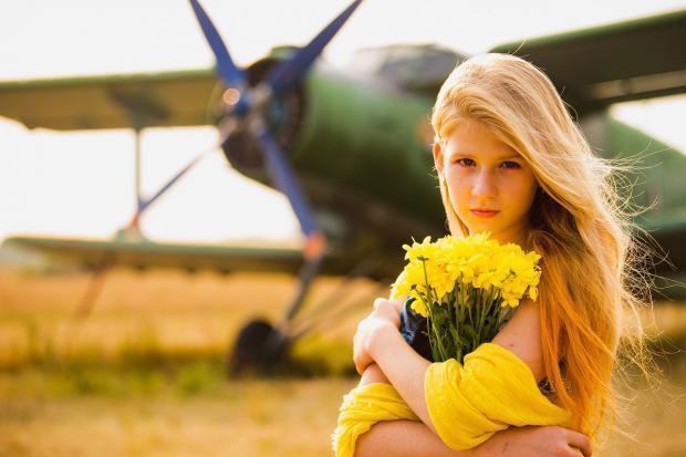девушка с желтыми цветами стоит на фоне самолета