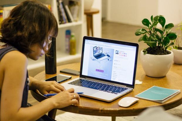 девушка работает в офисе с ноутбуком