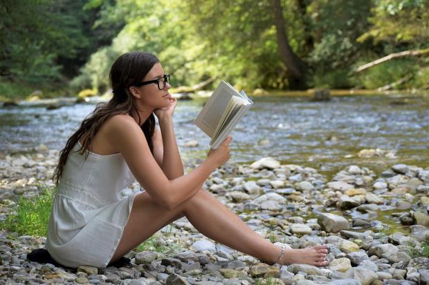 девушка сидит на берегу реки и читает книгу