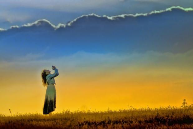 девушка с поднятыми в мольбе руками обращается к небу