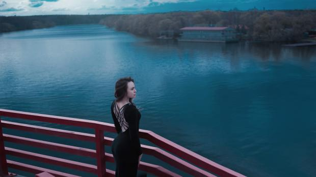 девушка с глубоким декольте на спине стоит на мосту