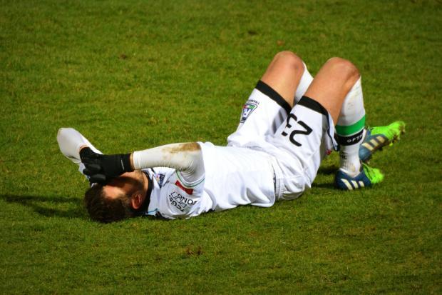 футболист лежит на футбольном поле