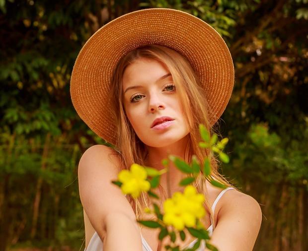 девушка в соломенной шляпе с желтыми цветами в руках