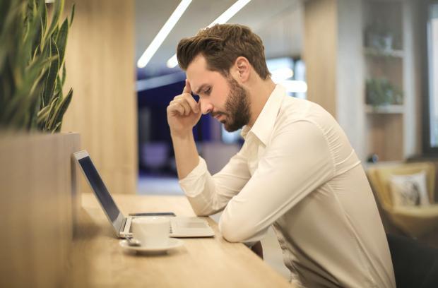 парень сидит перед компьютером и думает