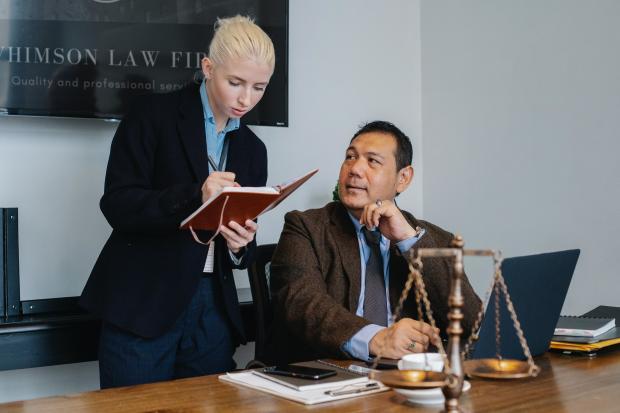 девушка с блокнотом стоит возле сидящего за столом мужчины