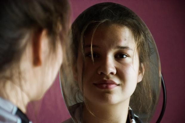 девушка смотрит в зеркало и улыбается