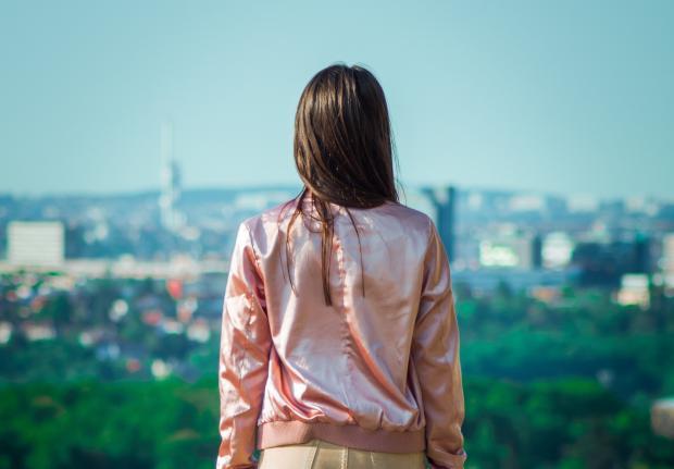 девушка в розовой куртке смотрит на город