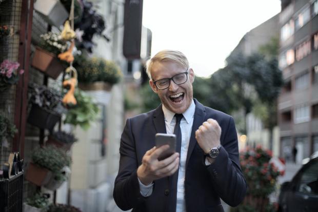 мужчина в очках с телефоном радуется, глядя на экран