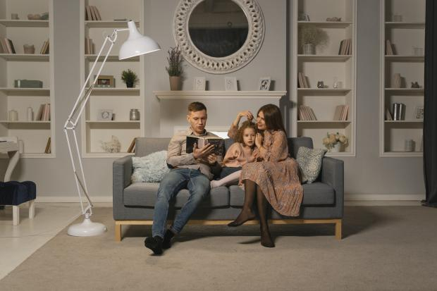 мама и папа с ребенком на диване, папа читает книгу
