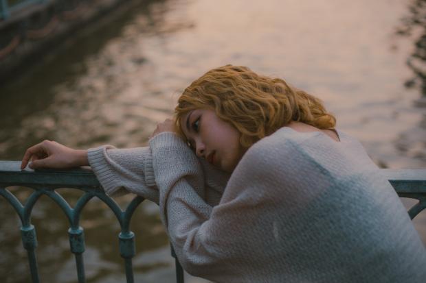 девушка с длинными волосами лежит головой на периллах