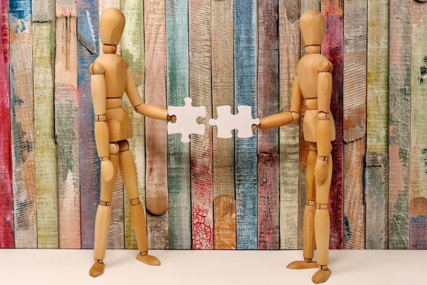 стоят две деревянные фигурки с деталями пазлов