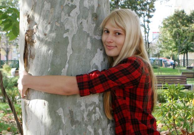 девушка в клетчатой рубашке улыбается и обнимает дерево