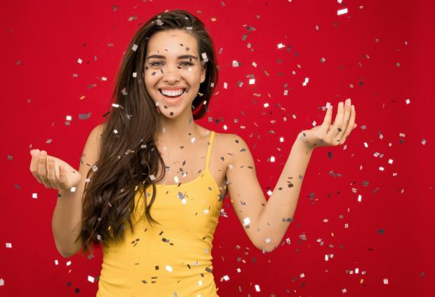 длинноволосая девушка в желтом сарафане смеется