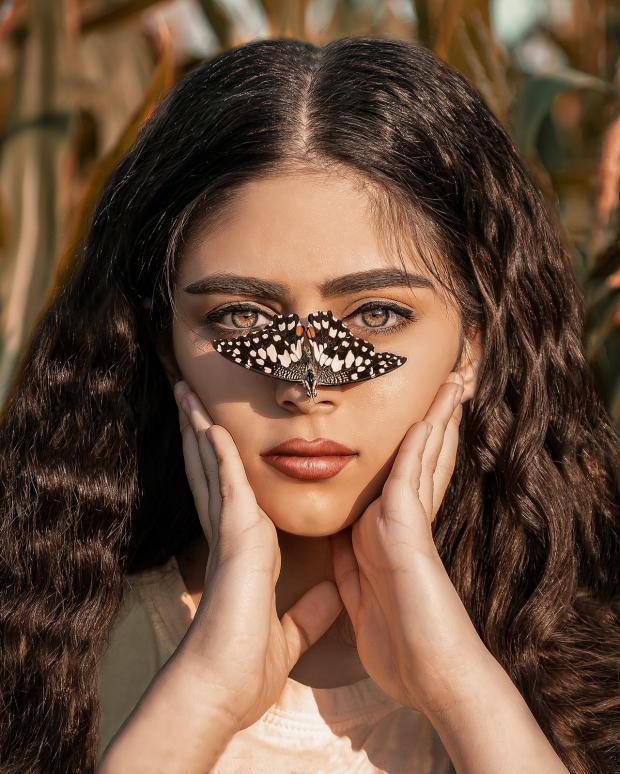у девушки с длинными волнистыми волосами на носу сидит бабочка