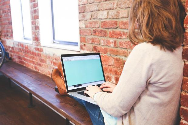 рыжеволосая девушка работает на ноутбуке на скамейке